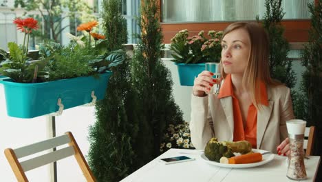 Businesswoman-Drinking-Water-And-Eating-Vegetables-And-Looking-At-Camera