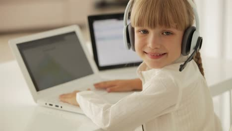 Cheerful-Little-Girl-In-Headset-With-Microphone-Sitting-At-Table-Using-Laptop