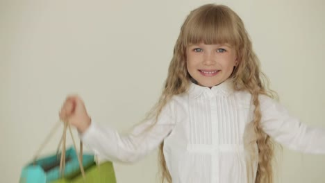 Cheerful-Pretty-Little-Girl-Posing-With-Multicolored-Paper-Bags