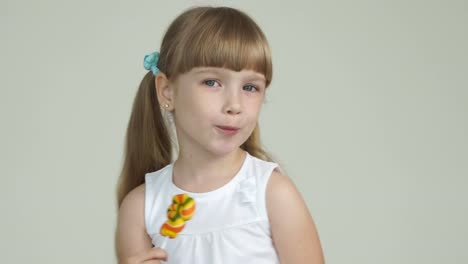 Cute-Girl-Licking-A-Lollipop-And-Smiling