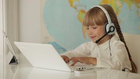 Niña-Linda-En-Auriculares-Sentado-En-La-Mesa-Con-Laptop-Y-Touchpad