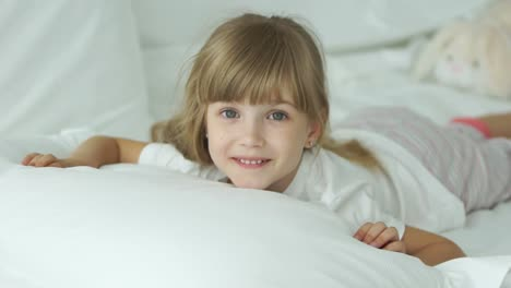 Cute-Little-Girl-Lying-In-Bed-And-Smiling-At-Camera