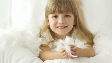 Cute-Little-Girl-Lying-In-Bed-Laughing-And-Playing-With-Pillow-Feathers