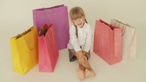 Cute-Little-Girl-Sitting-On-Floor-Surrounded-By-Shopping-Bags-Gesturing