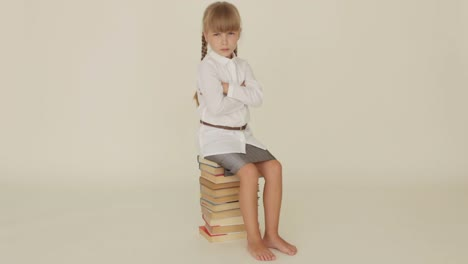 Funny-Little-Girl-Expressing-Discontent-Sitting-On-Pile-Of-Books-And-Shaking