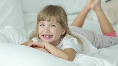 Funny-Little-Girl-Lying-In-Bed-Smiling-And-Laughing