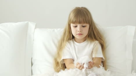 Funny-Little-Girl-Playing-With-Pillow-Feathers-And-Laughing