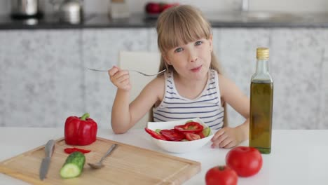 Funny-Little-Girl-Sitting-At-Kitchen-Table-And-Eating-Vegetable-Salad