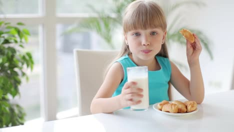 Funny-Little-Girl-Sitting-At-Table-Drinking-Milk-And-Eating-Cakes-And-Smiling