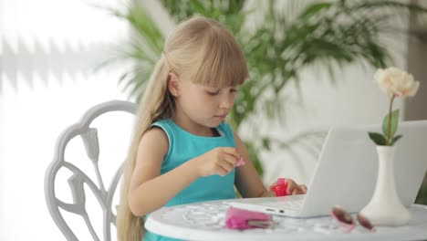 Funny-Little-Girl-Sitting-At-Table-With-Laptop-In-Front-Of-Her-And-Painting