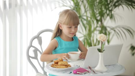 Funny-Little-Girl-Sitting-At-Table-With-Plate-Of-Biscuits-And-Cup-Of-Tea