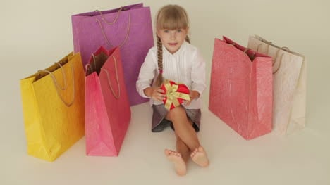 Funny-Little-Girl-Sitting-On-Floor-Surrounded-By-Shopping-Bags-Holding-Hearts