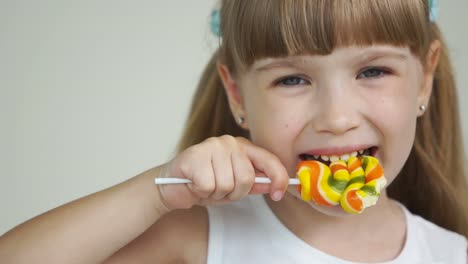 Girl-Biting-A-Lollipop-And-Smiling