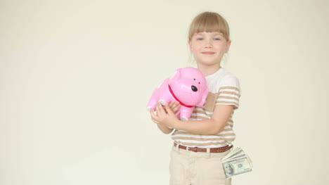 Mädchen-Hält-Ein-Sparschwein-Mit-Münzen-Und-Zeigt-Ok