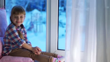 Girl-Looking-Out-The-Window-At-The-Snow-Covered-Playground
