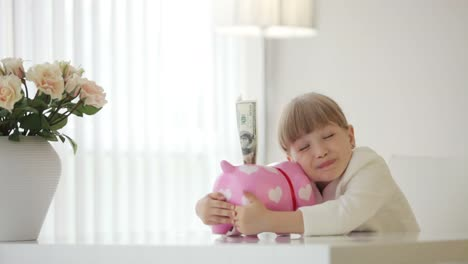 Girl-Sitting-At-The-Table-And-Hugging-Piggy-Bank
