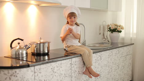 Girl-Sitting-On-The-Kitchen-Table-With-A-Ladle-And-Smiling-03