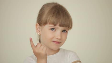 Mädchen-Winkt-Mit-Dem-Finger-Und-Schaut-Ernsthaft-In-Die-Kamera