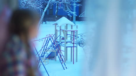 Happy-Child-Looking-Out-The-Window-At-The-Snow-Covered-Playground