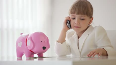 Little-Businesswoman-Talking-On-The-Phone-And-Holding-Money-In-Hand