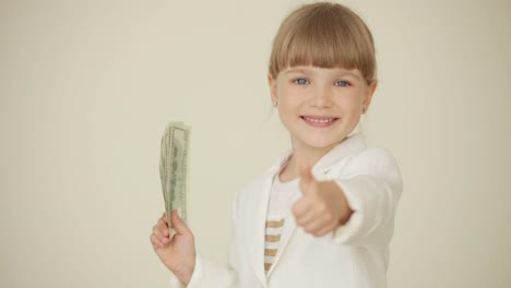 Little-Girl-Holding-Dollars-In-Her-Hand-And-Waving-Their