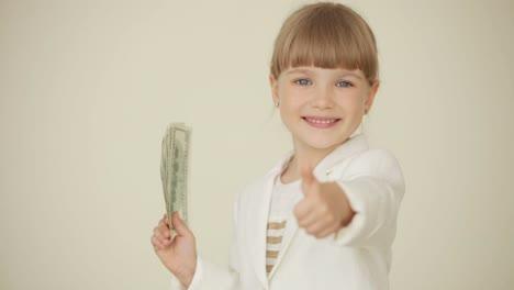 Kleines-Mädchen-Das-Dollar-In-Der-Hand-Hält-Und-Mit-Ihnen-Winkt