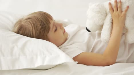 Little-Girl-Lying-In-Bed-And-Playing-With-Teddy-Bear