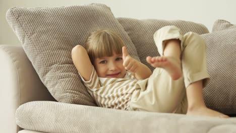 Little-Girl-Lying-On-Sofa-With-Ok-Hand-Sign