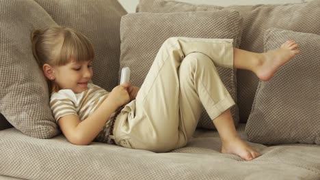 Little-Girl-Lying-On-The-Sofa-And-Writing-Sms