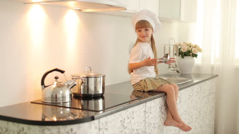 Little-Girl-Sitting-In-The-Kitchen-With-A-Ladle-In-Hand