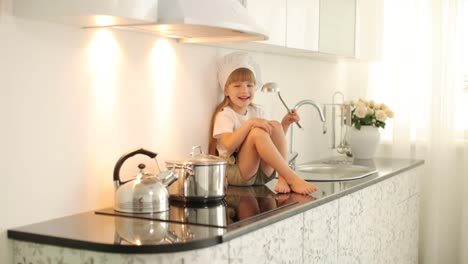 Little-Girl-Sitting-With-A-Ladle-In-The-Kitchen