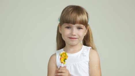 Little-Girl-Stands-With-A-Lollipop-And-Smiling