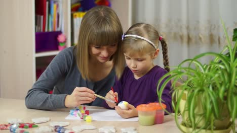 Mother-And-Child-Decorate-An-Easter-Egg-Looking-At-Camera