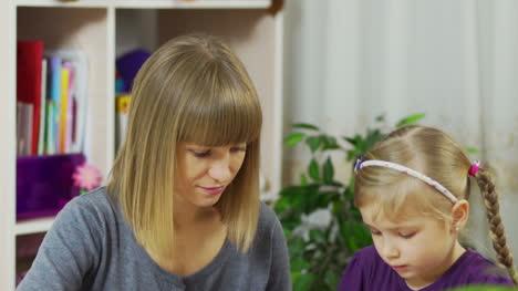 Mutter-Bringt-Einem-Kind-Bei-Farben-Zu-Malen-Das-Mädchen-Ist-Mit-Dem-Zeichnen-Beschäftigt