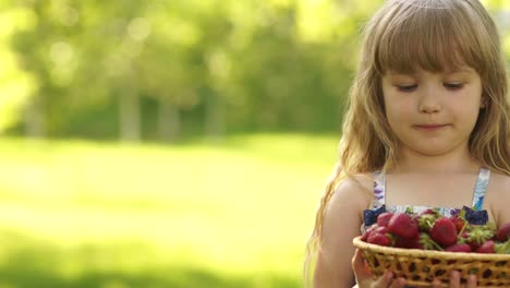 Portrait-Of-A-Smiling-Child-With-A-Basket-Of-Strawberries