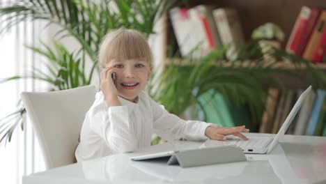 Pretty-Little-Girl-Using-Laptop-Talking-On-Mobile-Teléfono-And-Looking-At-Camera