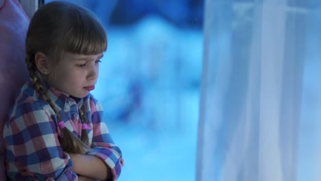 Sad-Child-Girl-Looking-Out-The-Window-At-The-Snow-Covered-Playground-Teasing