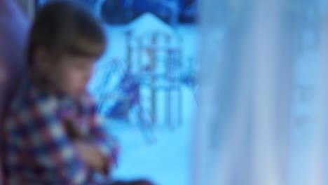 Trauriges-Kind-Das-Aus-Dem-Fenster-Auf-Den-Schneebedeckten-Spielplatz-Schaut