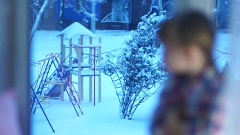 Sad-Girl-Looking-In-Window-At-The-Snow-Covered-Playground