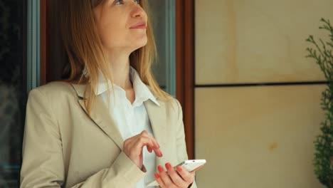 Empresaria-Usando-Un-Teléfono-Celular-Y-Mirando-A-Cámara