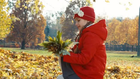 Child-Collects-A-Bunch-Of-Autumn-Leaves-In-The-Park