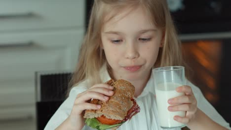 Child-Drinking-Milk-And-Eating-A-Sandwich
