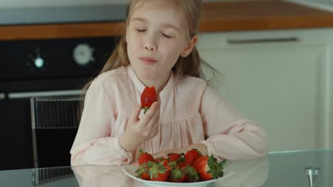 Child-Eating-A-Big-Red-Strawberry-And-Looking-At-Camera-And-Laughing
