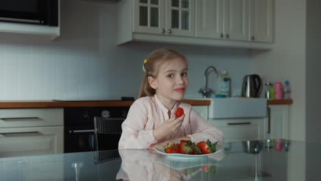 Child-Eating-A-Big-Red-Strawberry-And-Looking-At-Camera-Ok