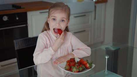Child-Eating-A-Big-Red-Strawberry-And-Looking-At-Camera-Top-View