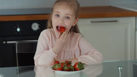 Child-Eating-A-Big-Red-Strawberry-And-Looking-At-Camera