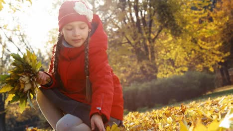 Child-Girl-Collects-A-Bouquet-Of-Autumn-Leaves-In-The-Park-And-Smiling-At-Cam