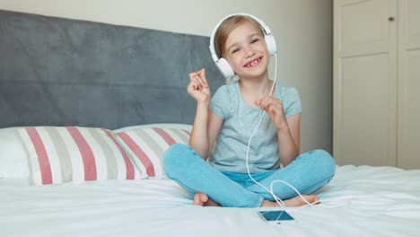 Girl-sitting-on-a-bed-and-listening-music-in-headphones-from-a-smartphone