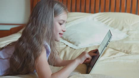 Child-Girl-Using-Tablet-PC-And-Looking-And-Smiling-At-Camera