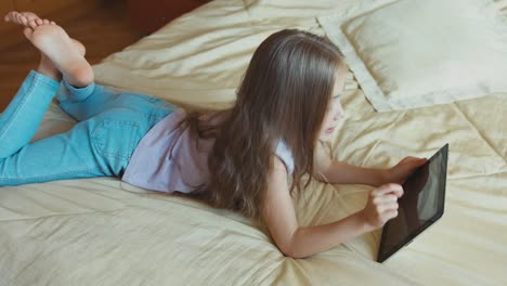 Child-Girl-Using-Tablet-PC-Lying-On-The-Bed-And-Smiling-At-Camera-Top-View